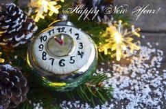 Gelukkig Nieuwjaar Kerstmisdecoratie met retro stuk speelgoed van wekkerkerstmis, denneappels en slingerlichten op oude houten ac Stock Foto