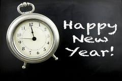 Gelukkig Nieuwjaar op bord met wekker Stock Afbeeldingen
