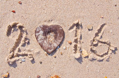 Gelukkig Nieuwjaar 2016 op de zand achtergrondtextuur en hart-Vormige kokosnotenshell Royalty-vrije Stock Afbeeldingen