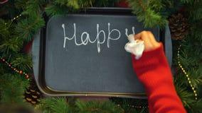 Gelukkig Nieuwjaar, vrouwelijk hand het schrijven woord met room op bakseldienblad, december stock footage