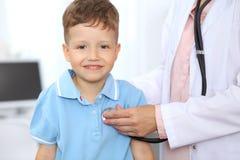 Gelukkig onderzoekt weinig jongen die pret hebben terwijl is door arts met stethoscoop Stock Afbeeldingen