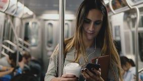 Gelukkig ontspannen zeker bloggermeisje op de metro die de speler app met behulp van die van de smartphonemuziek met koffiekop gl stock footage