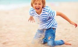 Gelukkig, opgetogen jong geitje, jongen die pret hebben, die in zand op het strand spelen Stock Afbeelding