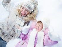 Gelukkig ouder en jong geitje die op sneeuw in de winter liggen Stock Afbeeldingen