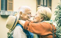 Gelukkig oudste teruggetrokken paar die pret het kussen hebben in openlucht in reistijd stock fotografie