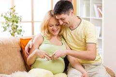 Gelukkig paar in afwachting van baby De glimlachende mens omhelst Stock Afbeeldingen