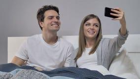 Gelukkig Paar in Bed die Selfie met Smartphone nemen, Foto stock footage