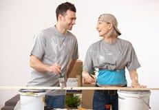 Gelukkig paar bij nieuw huis die pret het schilderen hebben Royalty-vrije Stock Foto