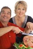 Gelukkig paar dat een ham snijdt royalty-vrije stock afbeeldingen