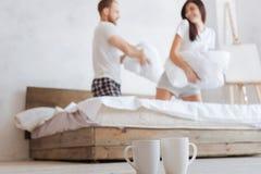 Gelukkig paar dat hoofdkussenstrijd in bed heeft stock afbeeldingen