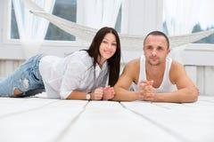Gelukkig paar dat op de vloer thuis ligt royalty-vrije stock afbeelding