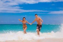 Gelukkig paar dat op het strand loopt Stock Foto's