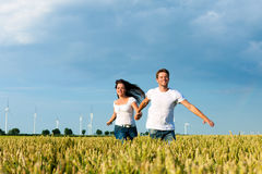 Gelukkig paar dat over grainfield loopt Royalty-vrije Stock Afbeeldingen