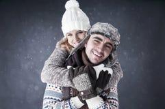 Gelukkig paar dat sneeuwachtergrond behandelt Stock Foto's