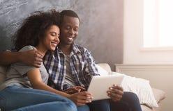 Gelukkig paar dat tablet gebruikt stock foto