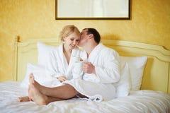 Gelukkig paar dat in witte badjassen koffie samen in bed drinkt bij ochtend stock fotografie