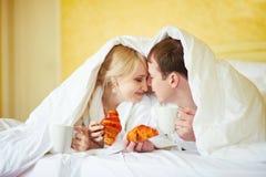 Gelukkig paar dat in witte badjassen koffie samen in bed drinkt bij ochtend stock foto's