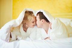 Gelukkig paar dat in witte badjassen koffie samen in bed drinkt bij ochtend royalty-vrije stock afbeelding
