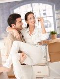 Gelukkig paar dat zich aan het nieuwe huis glimlachen beweegt Stock Afbeelding