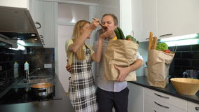 Gelukkig paar in de keuken De vrouwenkoks, de Man brengt de Zakken Voedsel stock video