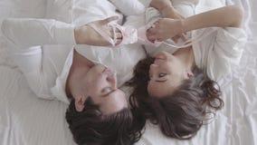 Gelukkig paar die in bed het spelen met roze kinderen pointe en het koesteren van close-up liggen Jonge familie die op een babyme stock footage