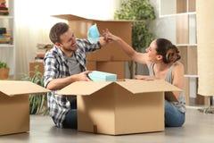 Gelukkig paar die beweegt naar huis in dozen doende bezittingen gekscheren stock fotografie
