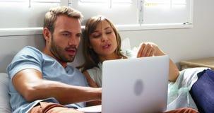 Gelukkig paar die bij bed gaan liggen die door Internet winkelen stock videobeelden