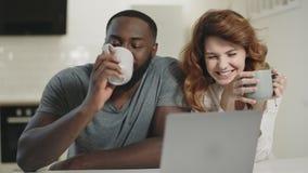 Gelukkig paar die bij open keuken spreken Glimlachende man en vrouw die laptop bekijken stock footage