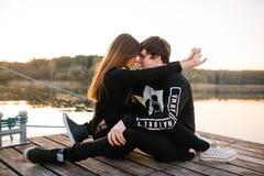 Gelukkig paar die bij zonsondergang op de pijler op een zonnige de zomerdag koesteren Het concept van de liefde Royalty-vrije Stock Afbeelding