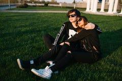 Gelukkig paar die bij zonsondergang op het gazon op een zonnige de zomerdag koesteren Het concept van de liefde Stock Afbeeldingen