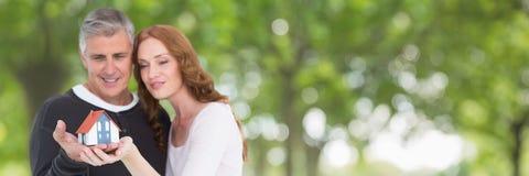 Gelukkig paar die een huis houden tegen groene achtergrond als concept verzekering stock afbeeldingen