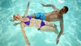 Gelukkig paar die in een pool zwemmen stock footage