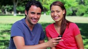 Gelukkig paar die een tekst op een mobiele telefoon bekijken stock videobeelden