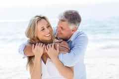 Gelukkig paar die elkaar koesteren door het overzees Stock Foto's