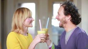 Gelukkig paar die en het drinken fruit smoothie roosteren stock videobeelden