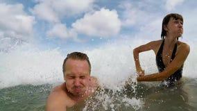 Gelukkig Paar die en in Oceaan golven zwemmen Wittebroodsweken die pret in ocan met grote golven hebben Tropisch eiland Bali stock video