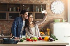 Gelukkig paar die en selfie in keuken koken nemen stock fotografie