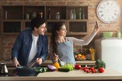 Gelukkig paar die en selfie in keuken koken nemen stock foto's