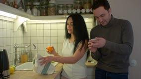 Gelukkig paar die en smartphone spreken gebruiken terwijl thuis het koken in keuken stock video
