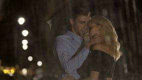 Gelukkig paar die en van elkaar koesteren genieten onder de regen, de hartstocht en de liefde stock video