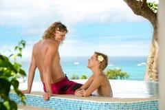 Gelukkig paar die en in zwembad glimlachen spreken stock afbeeldingen