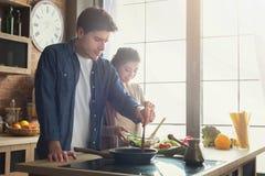 Gelukkig paar die gezond diner samen koken stock afbeelding
