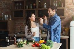 Gelukkig paar die gezond voedsel samen koken stock afbeelding