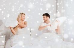 Gelukkig paar die hoofdkussenstrijd in bed hebben thuis Royalty-vrije Stock Foto