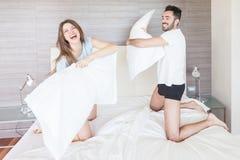Gelukkig Paar die Hoofdkussenstrijd hebben Royalty-vrije Stock Afbeeldingen