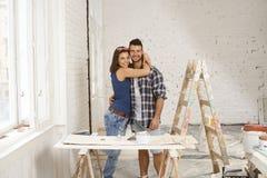 Gelukkig paar die in huis in aanbouw omhelzen royalty-vrije stock foto