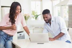 Gelukkig paar die hun laptop met behulp van bij ontbijt Stock Afbeeldingen