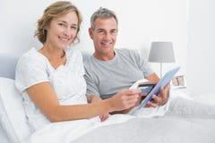 Gelukkig paar die hun tabletpc met behulp van online te kopen royalty-vrije stock fotografie