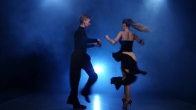 Gelukkig paar die jive in rokerige studio met blauwe schijnwerper dansen stock video