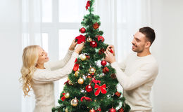 Gelukkig paar die Kerstmisboom thuis verfraaien Stock Afbeeldingen